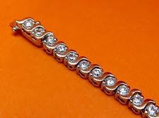"""Afbeelding van """"Zwierige zirkonia"""" tennisarmband in sterling zilver en ronde kubiek zirkonia met golvende streepjes"""
