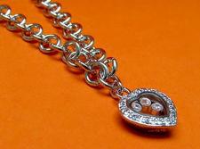 """Afbeelding van """"Speelse"""" armband in sterling zilver, rolo schakel ketting met hartvormig bedeltje omringd door kubiek zirkonia en daarin zwevende zirkonia"""