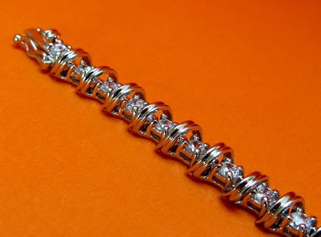 """Picture of """"Spiraling in Zirconia """" tennis bracelet in sterling silver, a row of prong set round cubic zirconia interspersed with spiraling waves"""