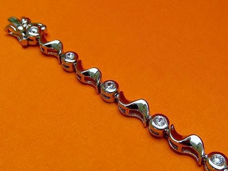"""Afbeelding van """"Golven van zirkonia"""" tennisarmband in sterling zilver, ronde kubiek zirkonia afgewisseld met zilveren golven"""